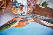 stock photo of canvas  - Male artist painting street of Venice on canvas - JPG
