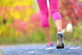 stock photo of athletic woman  - Jogging and running woman with athletic legs on jog or run on trail in forest in healthy lifestyle concept with close up on running shoes - JPG