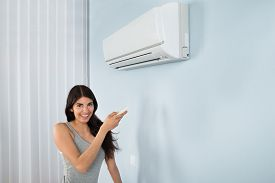 picture of house representatives  - Young Happy Woman Holding Remote Control Air Conditioner In House - JPG