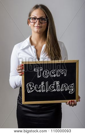 Team Building - Young Businesswoman Holding Chalkboard With Text