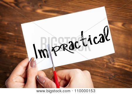 Woman hands cutting card with the word impractical