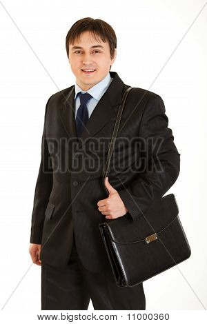Smiling young businessman holding briefcase on shoulder