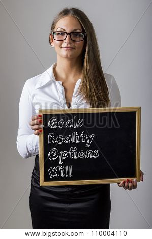 Goals Reality Options Will Grow - Young Businesswoman Holding Chalkboard With Text