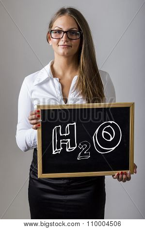 H2O - Water Molecule  - Young Businesswoman Holding Chalkboard With Text