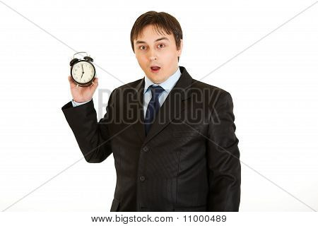 Shocked young businessman holding alarm clock. Lost time concept