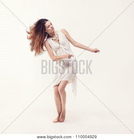 young beautiful dancer in white dress posing