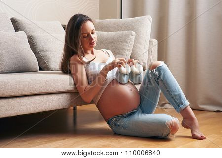Pregnant woman holding small baby shoes relaxing at home by the couch