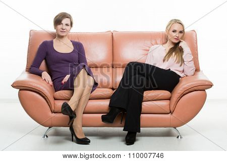 beautiful female friends on the sofa. two businesswomen. body language, gestures psychology. paired