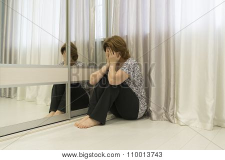Woman with depression sitting in  corner of the room