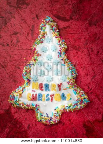 Christmas tree-like gingerbread cookie with white icing on red background