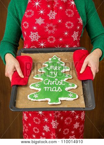 Goodwife holding a baking tray with home-made christmas tree-like gingerbread cookie with green icing and Merry Christmas writing