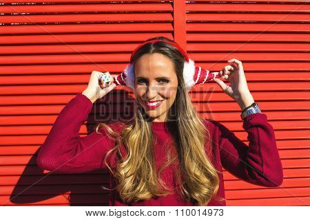 Portrait Of Woman With Earmuffs Christmas; On Red Background