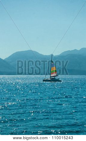 Sailing Boat Floats On A Background Of Mountains