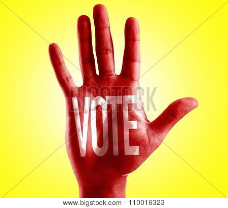 Vote written on hand with yellow background