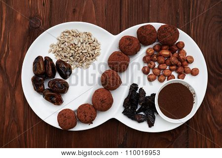 set of raw food and seperfood dessert on white plate over wood background