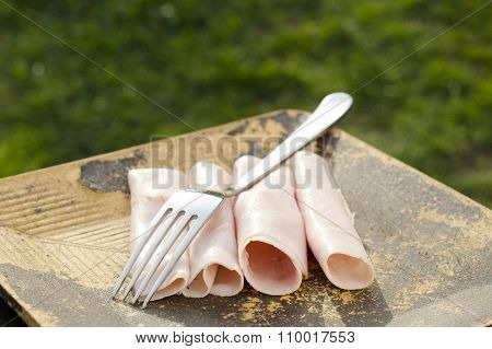 ham and fork on a wooden table and green background. breakfast on a wooden plate