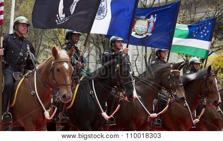 NEW YORK - NOV 25 2015: Members of the NYPD Mounted Unit Honor Guard carry flags while riding on horseback in the annual Americas Parade up 5th Avenue on Veterans Day in Manhattan.