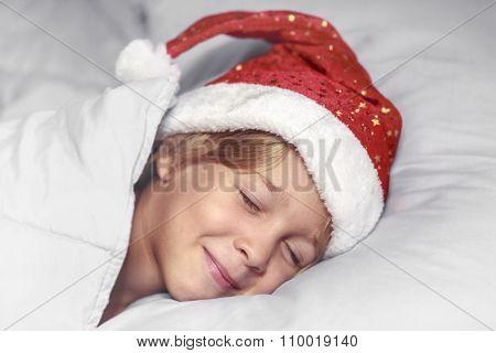 Boy in Santa hat sleeping on a pillow