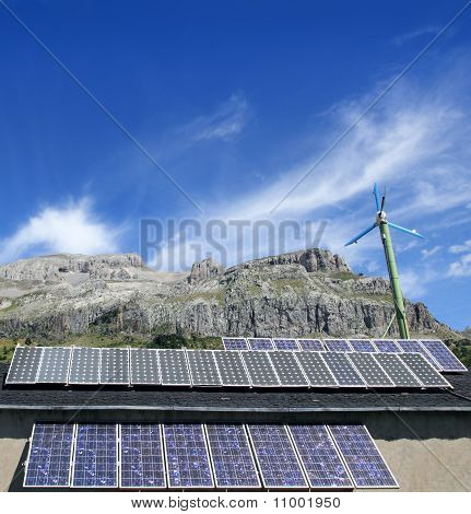 Solar Plates And Windmill  Under Blue Sky