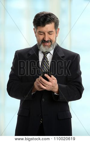 Mature Hispanic businessman using cellphone inside office building