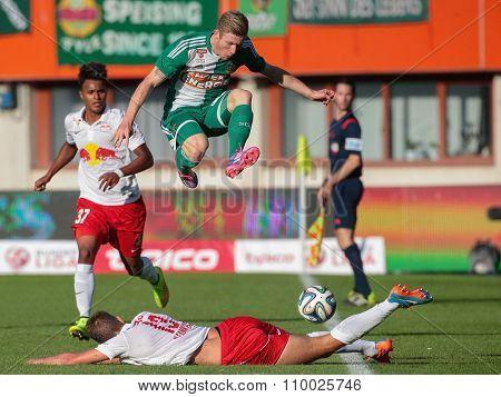 VIENNA, AUSTRIA - SEPTEMBER 28, 2014: Florian Kainz (#14 Rapid) jumps over Stefan Ilsanker (#13 Salzburg) in an Austrian soccer league game.