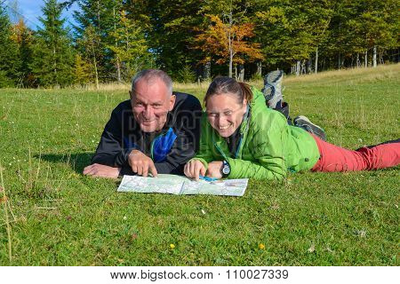 Happy Hikers Couple Are Having Fun , When They Are Planning Their Route.