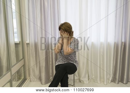 Woman in depression sits on a chair