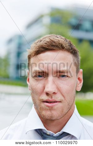Portrait of a serious young businessman in the city