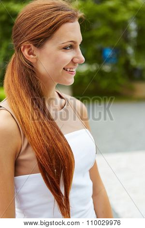 Smiling young woman standing outdoors in the summer