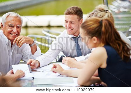Successful business team doing planning in a meeting outdoors at a table