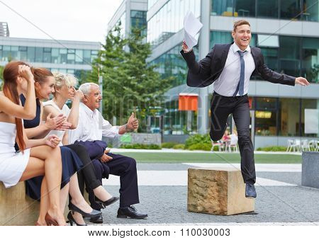 Team cheering for business man jumping over an obstacle for motivation
