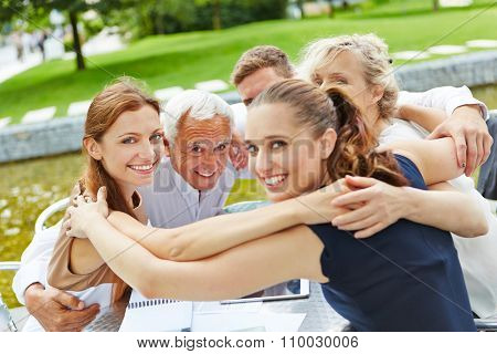 Group of business people hugging for motivation in a business team