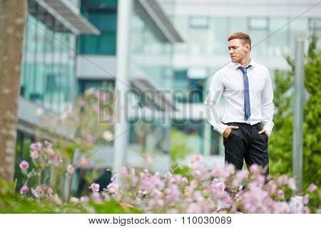 Businessman standing pensive in the city in front of an office building