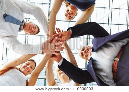 Cooperation and teamwork in business team with many hands stacked on a pile