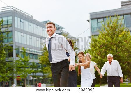Successful business team holding hands while running outdoors together