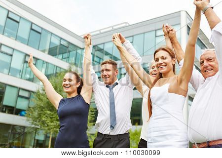 Happy cheering business team holding together the hands up