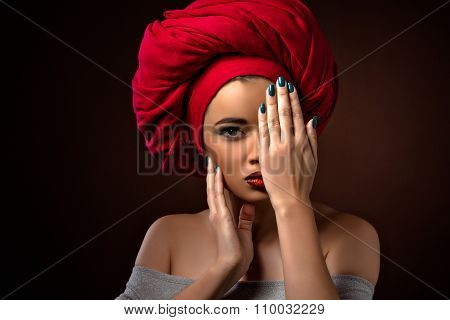 Beautiful latin girl hiding behind her palm isolated on dark