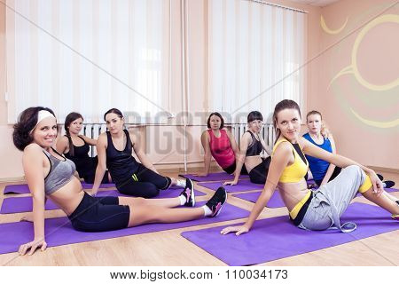 Sport, Training Anf Healthy Lifestyle Concepts. Group Of Seven Caucasian Women Resting On Floor Mats