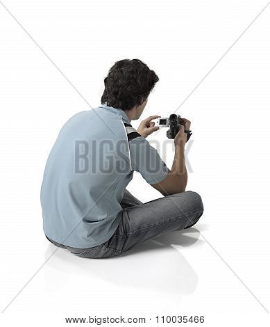 Man sitting on his back with camcorder