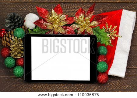 A black tablet computer with blank white screen on top of glittery Christmas decoration on brown wooden background