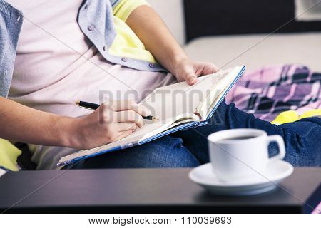 a girl writes down in a notebook sitting on a sofa