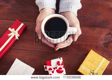 coffee in hands with gifts on a wooden background