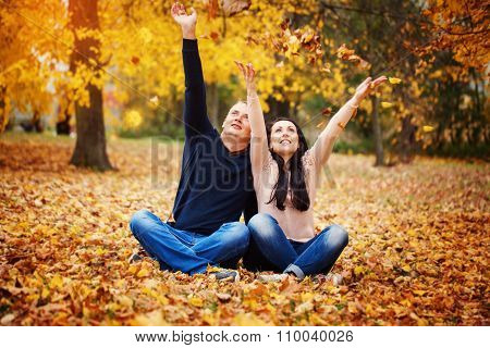 Positive And Carefree Couple Having Fun  Tossing Leaves In Autumn Park.