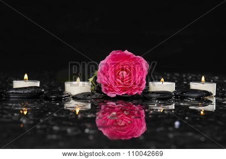ranunculus with white candle and therapy stones