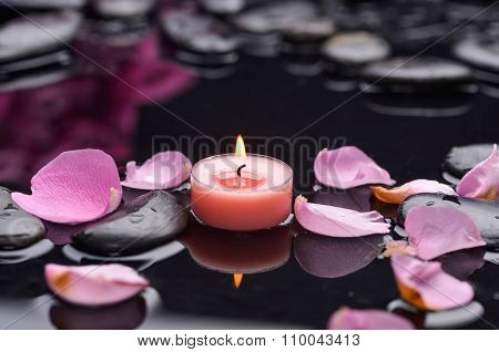 Pink rose petals with candle and therapy stones
