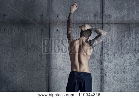 Sport fit muscular tattooed guy from back