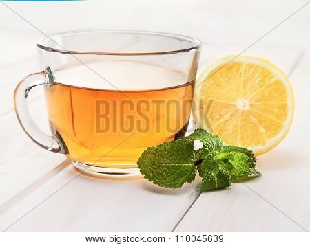 cup of tea, mint and lemon on a wooden table