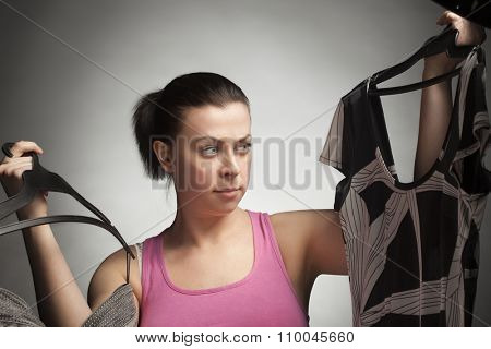 Girl chooses a dress suit isolate on grey