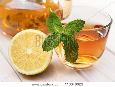 cup of tea, glass teapot, mint and lemon on a wooden table