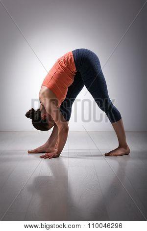 Sporty fit woman stretching in Ashtanga Vinyasa yoga asana Parsvottanasana - intense side stretch pose